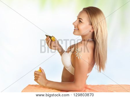Beautiful young girl using sunscreen on the beach to protect her skin from sunburn, healthy sunbathing, woman enjoying happy summer vacation