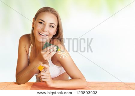 Portrait of a beautiful happy woman applying sunblock, tanning on the beach, young adult girl enjoying summer holidays, healthy lifestyle and skin protection concept