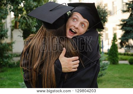 Young man in cap and gown playfully hugged her friend. She is also a graduate of the University.