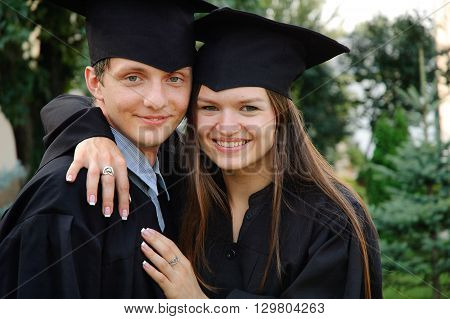 Beautiful girl in gown and hat hugging a fellow student. Graduates of fun watching the camera