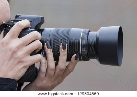 girl with beautiful manicure photographs on single-lens reflex camera