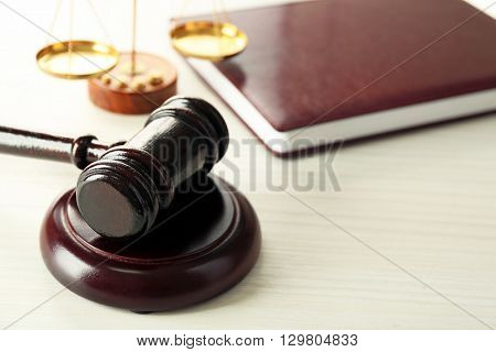 Gavel with book and scales on wooden background