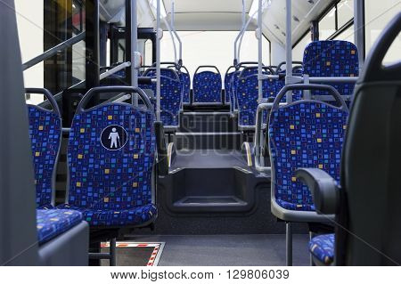Bus inside, city transportation white interior with blue seats in row, retirement places, open doors, handles for standing passengers, bright lights and air conditioner