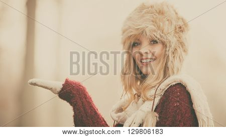 Portrait of pretty smiling fashionable woman in fall forest park. Happy gorgeous young girl in fur winter hat with empty palm hand for advertisement. Autumn fashion copyspace.