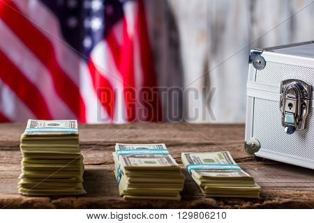 American flag, dollars and case. Dollar bundles near silver suitcase. Find your source of income. Progress of economy.