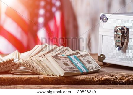 Dollars, case and USA flag. Money bundles beside silver case. Business is power. All the ways are opened.
