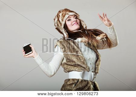 Winter girl listening music using phone with headphones raising hand. Happy woman wearing fur vest and warm hat in freezing cold time.