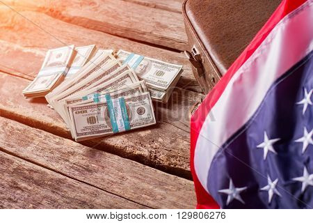 American flag, cash and suitcase. Money bundles laying beside case. Prosperity and progress. Work and respect the country.