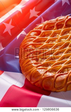 American flag and a pie. Pie laying on bright banner. Traditions of great country. Hospitality and peace.