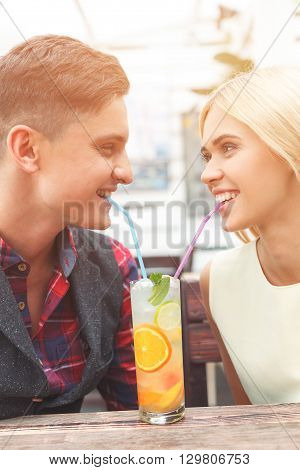 Cute man and woman are sharing on glass of cocktail. They are drinking it though straws and smiling. Lovers are sitting at table in cafe