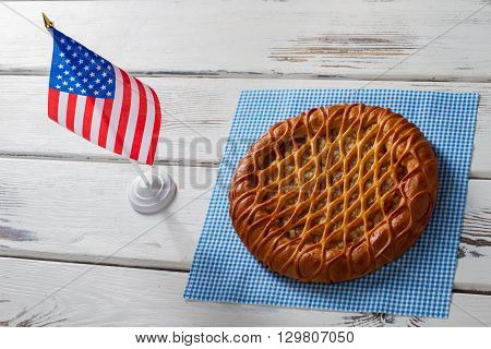 American flag beside round pie. Pie, napkin and small flag. Traditional pie served at cafe. New dish in the menu.