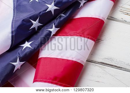Crumpled flag of USA. Banner on white wooden background. Pride, freedom and democracy. Homeland of great inventors.