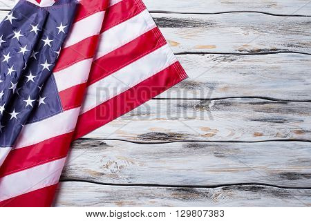 Creased USA flag. National flag on wooden background. Freedom and solidarity. Country driven by democracy.