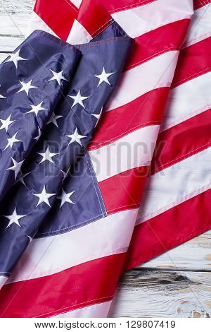 Creased flag of America. Flag on white wooden background. Bright stripes and stars. Banner of proud people.