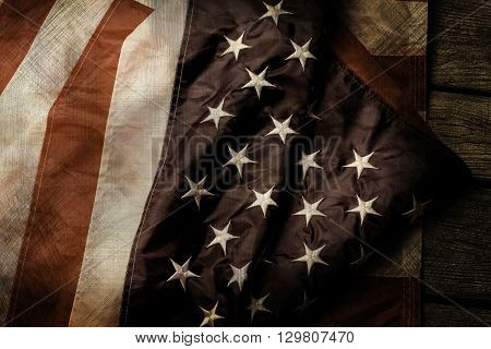 Aged and crumpled US flag. Old flag on wooden background. Courage, honor and loyalty. Fallen shall be forever remembered.