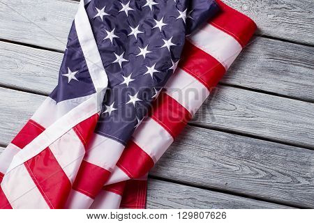 Creased and crumpled US flag. US banner on wooden background. Freedom of speech and choice. Strong laws and developed society.