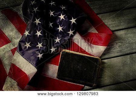 Aged USA flag and book. Book laying beside national flag. Law will protect you. In God we trust.