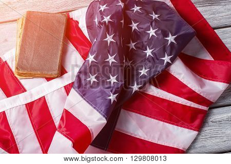 Creased USA flag and book. Banner and book under sunlight.
