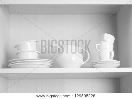 Tableware on shelf in the kitchen cupboard