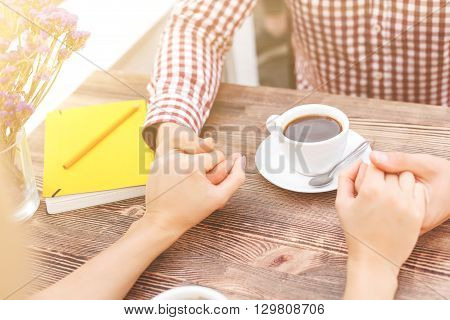 Close up of loving couple holding hands. They are sitting at table near a cup of coffee