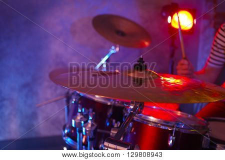 Drummer playing on drum set on stage.