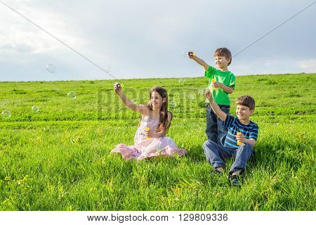 Three kids blowing up the soap bubbles on sunny green lawn, empty space for text