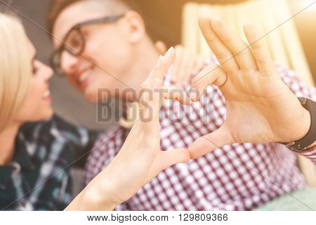 Beautiful loving couple is sitting and embracing. They are making hear while joining their hands. The man and woman are smiling with love