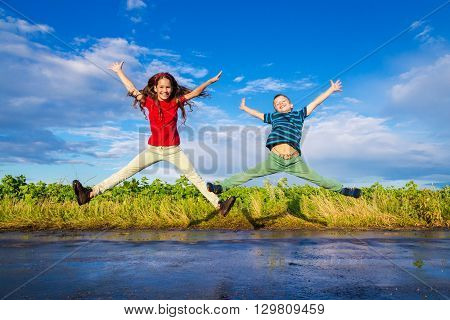 Happy kids jumping on wet road after rain
