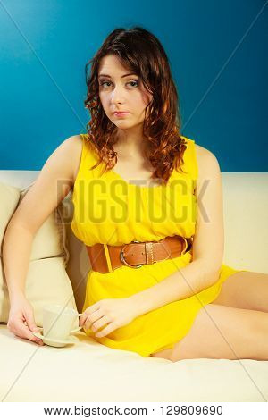 Beauty fashion and relax concept. Fashionable girl yellow dress holding hot drink coffee or tea cup sitting on sofa dark blue background