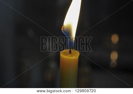 yellow candle burning with a bright flame in the dark