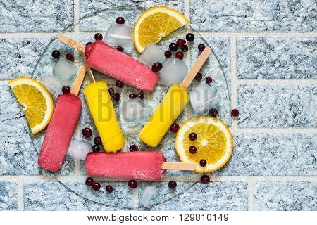 Delicious fruit ice with orange and cranberries and ice on a glass tray. Top view