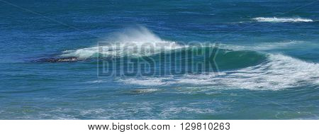 Nature background Turquoise pacific water. Splashing wave.