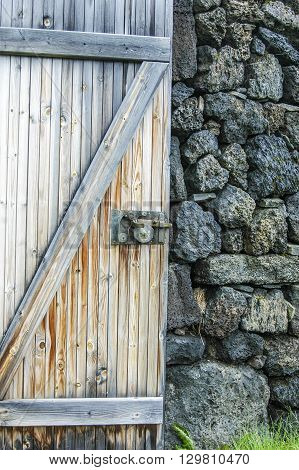 A detail of an open rustic barn door against a stone wall with blades of green grass.