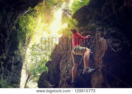 young woman rock climber climbing at mountain cliff