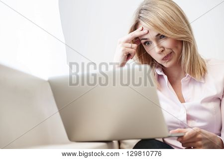 Beautiful blond girl is working on a laptop. She is sitting on sofa at home. The lady is looking at screen pensively