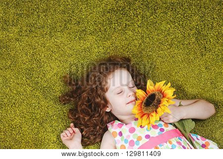 Cute child with sunflower sleeping on the green carpet.