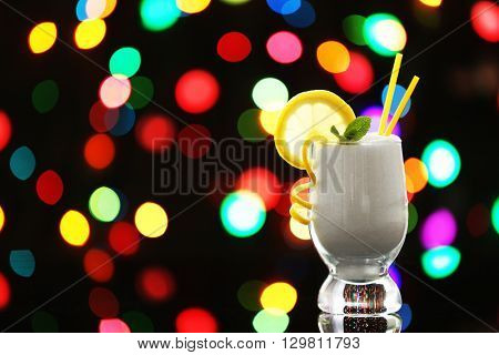 Tumbler glass with granulated sugar on dark bokeh background