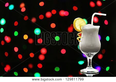 Hurricane glass with granulated sugar on dark bokeh background