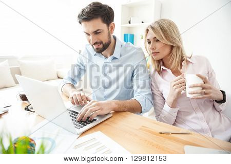 Skillful two colleagues are working in cooperation. Man is typing on laptop and smiling. Woman is sitting near him and looking at screen with interest. She is drinking coffee