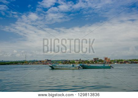 Muisne, Ecuador - March 16, 2016: Traditional fishing boats tied together at sea, city in background and beautiful blue sky.
