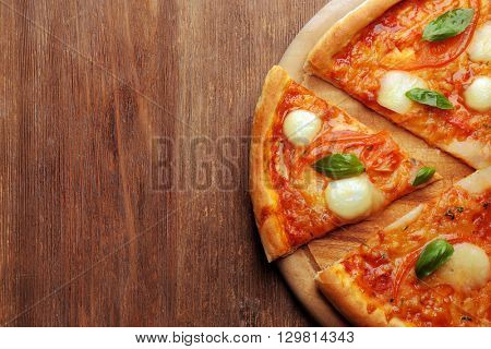 Sliced Margherita pizza on wooden background
