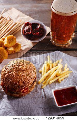 Big tasty hamburger with snacks and glass mug of light beer on wooden table