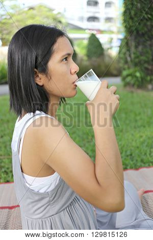 Asia pregnant mom was drinking milk in the garden for good health.