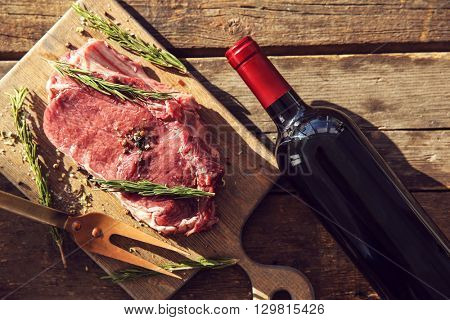 Raw pork steak with bottle of red wine, meat fork and rosemary on wooden background