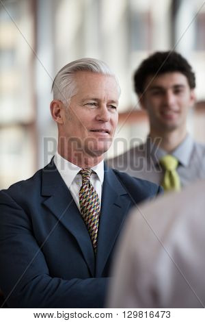 portrait of senior businessman as leader  at modern bright office, business  team  people group in background
