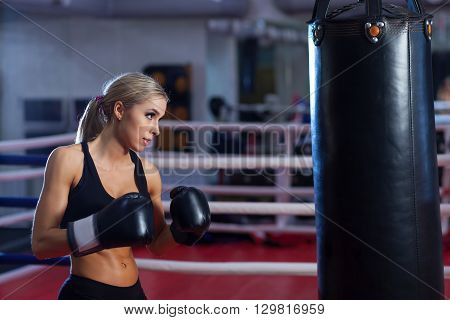 Young pretty boxer woman standing on ring and doing exercise with punching bag