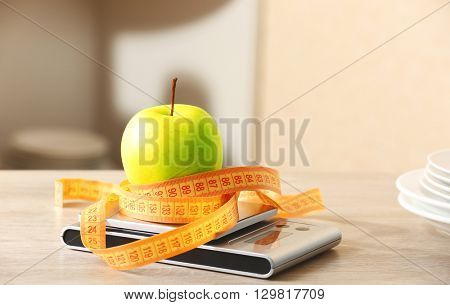 Apple with centimeter and digital kitchen scales on wooden table