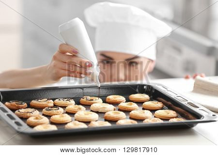 Professional confectioner cooking delicious dessert at kitchen