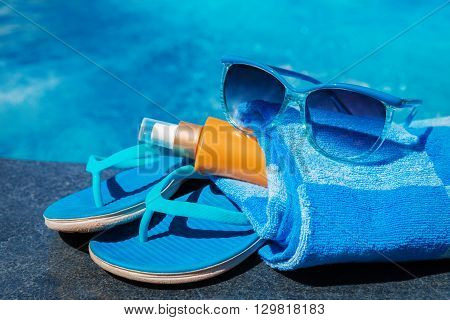 Blue slippers, sunsscreen cream and sun glasses near swimming pool - holiday concept
