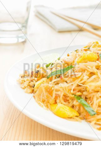Pad Thai or Thai fried noodles on white dish on wood table vertical style. Glass and napkin chopsticks egg dry shrimps onions sprouts lemon peanut